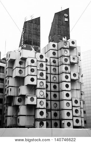 TOKYO, JAPAN - 22 JUNE 2016: The iconic Nakagin Capsule Tower in Shimbashi,Tokyo. Built in 1972  designed by Kisho Kurosawa and a rare surviving example of Japanese Metabolism style. Black and white.
