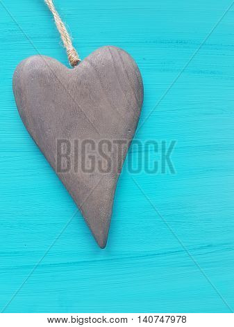 wooden heart shape on a turquoise wooden background