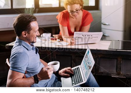 Know what is around you. Joyful mature bearded man sitting with the laptop and reading news while his wife with glasses reading a newspaper on the background