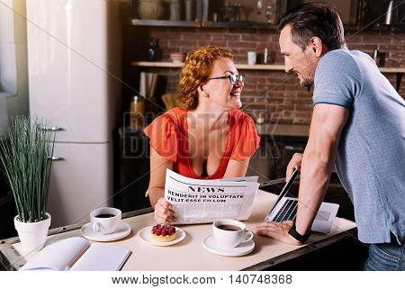 You are so beautiful today. Charming middle aged woman with glasses reclining on the table and reading news while her handsome mature man looking at her