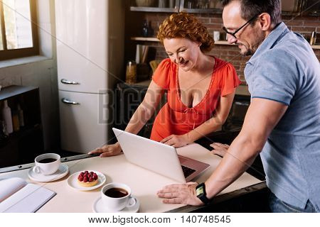 Thats amazing. Interested middle aged woman looking and wise mature man looking at the screen of the laptop