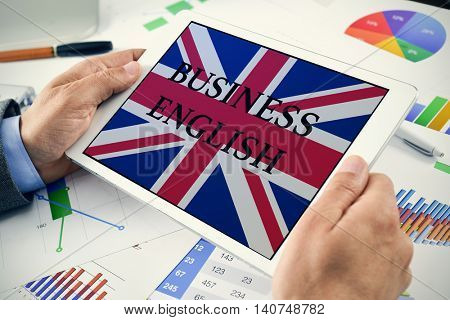 closeup of a young caucasian businessman at his office desk full of charts showing a tablet computer with the text business English and the flag of United Kingdom in its screen
