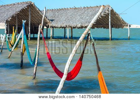 Hammocks and beach chairs under the shade of a palapa sun roof umbrella in Jericoacoara Brazil