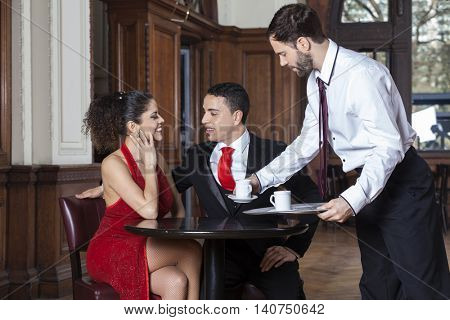 Waiter Serving Coffee To Tango Couple In Restaurant