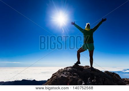 Woman successful hiking climbing silhouette in mountains motivation and inspiration landscape on island and ocean. Hiker with arms up outstretched on top looking at beautiful view on Tenerfie Spain.