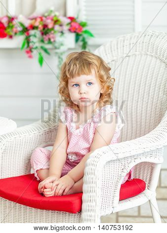 Little cute curly girl sitting on white wicker chair in the garden and looks into the distance.