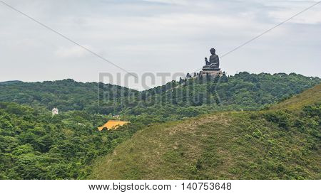 The Tian Tan Buddha on the mountain in Ngong Ping Hong Kong in a cloudy day.