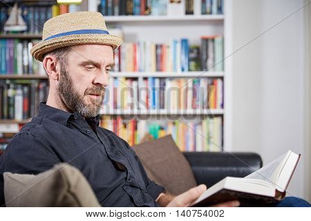 Student With Hat Sitting In Front Of A Book Shelf Reading