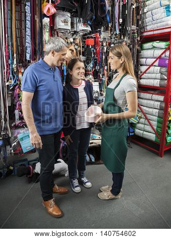 Saleswoman Showing Heart Shape Pet Food Bowl To Family