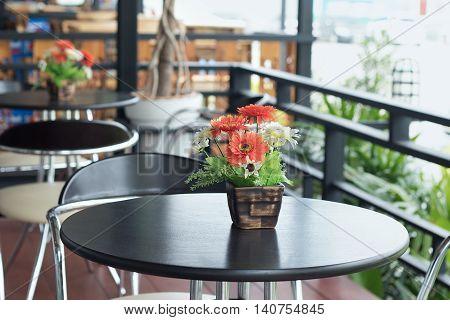 artificial flowers in flowerpot on coffee table