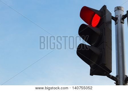 red color on the traffic light with a clear beautiful blue sky in background.