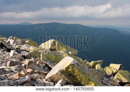 Mountain landscape. Amazing wild nature view of deep evergreen forest landscape on sunlight at middle of summer. Natural green scenery of cloud stones with moss on mountain Ukraine Carpathians.
