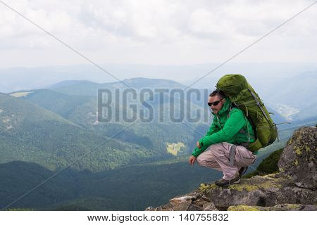 Happy hiker winning reaching life goal success freedom and happiness achievement in mountains. Hiker with backpack on top of a mountain.