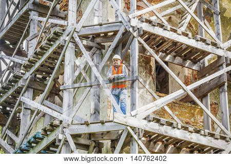 Construction worker with tablet PC on wooden scaffolding