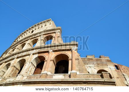 Flavian Amphitheatre or Colosseum in Rome with blue sky in the background, Italy