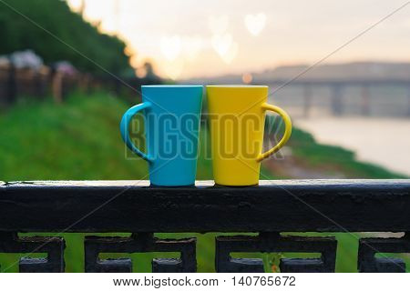 Two mugs on the railing. A pair of cups of tea coffee. Bright circles yellow and blue. Summer evening. Concept for lovers. Bokeh Heart.