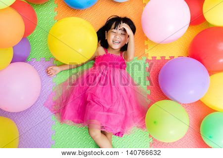 Asian Little Chinese Girl Lying On The Floor Amongst Colorful Balloons