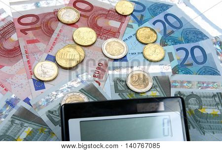 Calculator with Euro notes and coins. Finance concept.