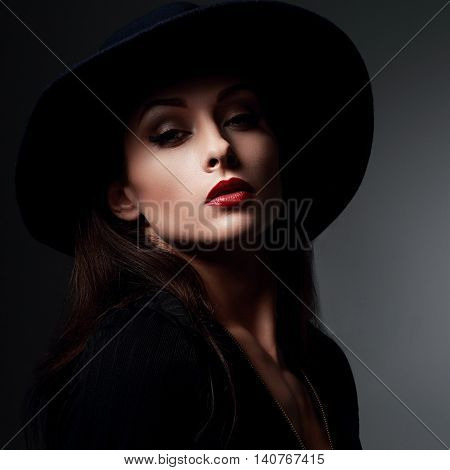 Elegant Makeup Woman In Fashon Hat And Red Lips Posing On Dark Shadow Background. Closeup Portrait