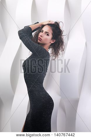 Sexy Figured Hispanic Makeup Woman Posing In Grey Dress On White Paper Background
