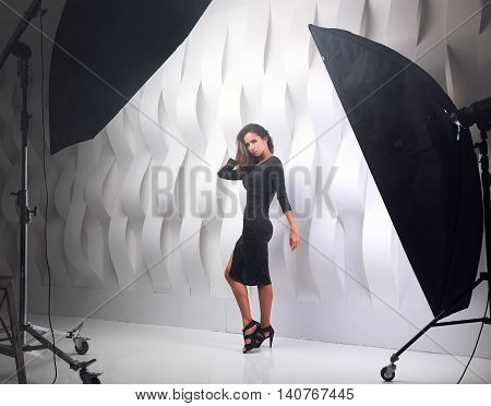 Photo session in studio of sexy posing model in evening dress and fashion heels on white paper creative background