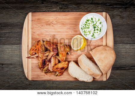 delicious grilled chicken wings with garlic sauce, lemon and bread on a cutting board on wooden rustic background, top view