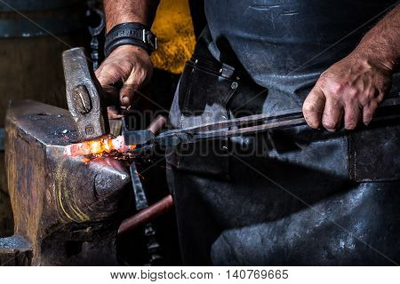 blacksmith working hard on a iron piece