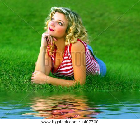 Cute Girl Lying Near The Rivershore
