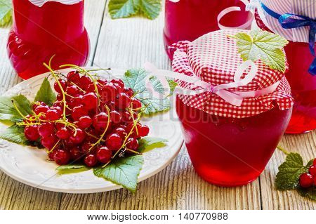 Preserved homemade red currant jam in glass jars on white wooden table. Fresh berries and green leaves vintage plate.
