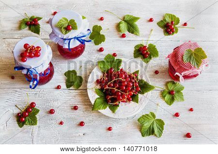 Preserved homemade red currant jam in glass jars on white wooden table. Fresh berries and green leaves vintage plate top view.