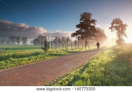 runner in countryside during misty summer sunrise