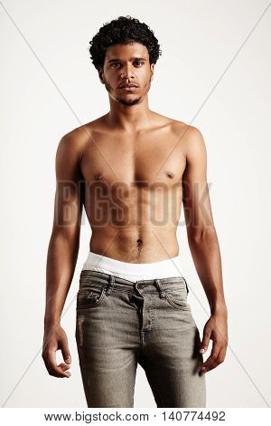 Young Man Wears Jeans, Showing Perfect Body. T-shirt Less