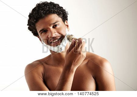 smiling man puts foam for shave and looking at camera
