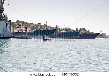 Boat in front of ships in harbor.