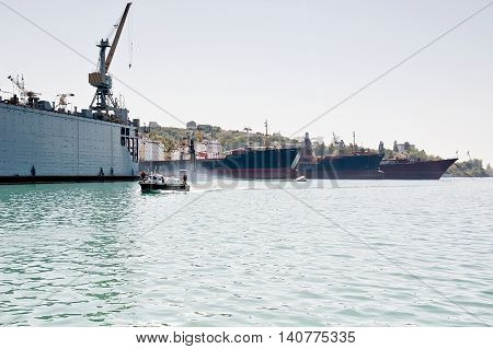 Boat in front of ships and floating dock in harbor.