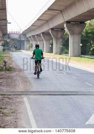 The modern bicycle is riding slowly under the express way near the city park.