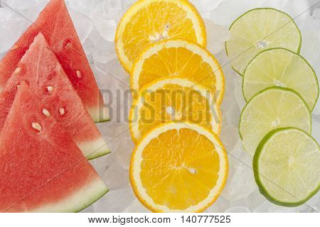 Rows of various fruit on ice. Watermelon orange and lime slices lined up on ice.