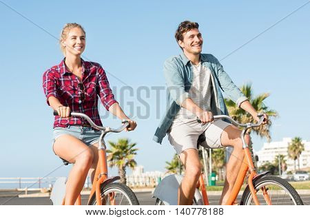 Active young couple riding bikes during summer vacation. Happy smiling girl and guy cycling through the street. Cheerful young man and woman riding their bicycles during sunset.