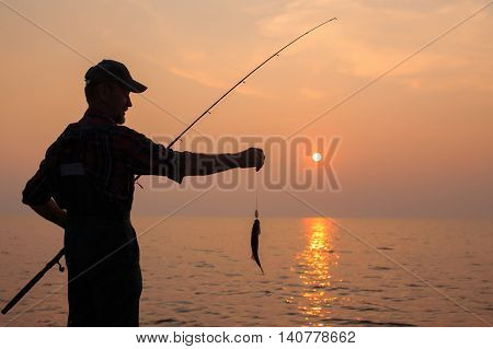 fisherman with a catch at sunset. elderly fisher proudly displays caught fish