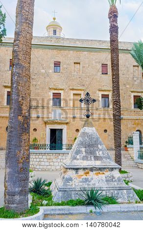 The small pyramid-shaped memorial stone with an iron cross on the top located in front of the Stella Maris Monastery Haifa Israel.