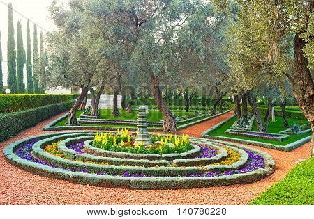 The round flower bed consists of many rows of colorful flowers with the Oriental park sculpture in the middle Bahai Gardens Haifa Israel.