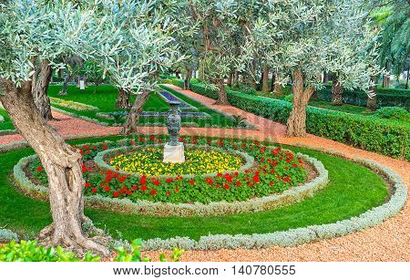The colorful flower bed with decorative vase was planted among the olive trees Bahai Gardens Haifa Israel.