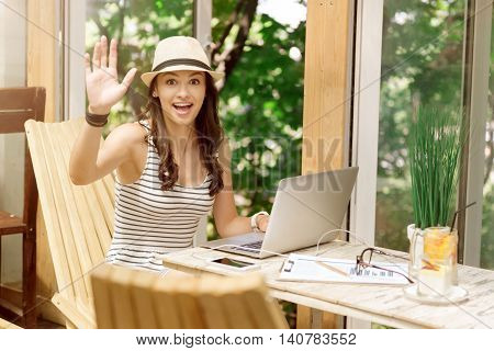 Hey you. Joyful charming smiling woman sitting at the table and using laptop while welcoming you