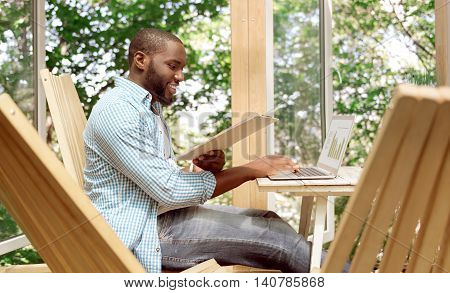 Multitasking in mind. Positive handsome smiling man holding folder and using laptop while sitting at the table