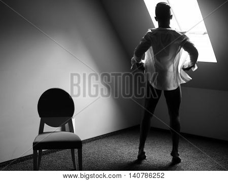 Muscular man undressing with white shirt standing near chair and looking out the window