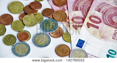 10 euro bills and metal coins and cents on a white background