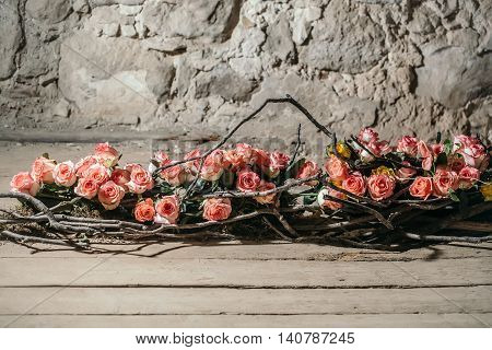 Floral arrangement with pink rose flowers and wooden twigs on wood floor and stony wall