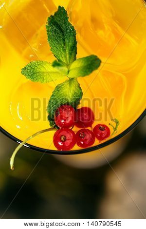 bright glasse with cold cocktail of orange juice decorated with viburnum and mint leaf closeup