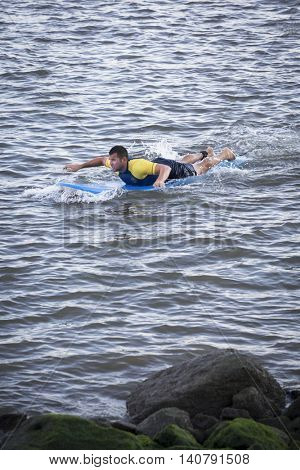NEW YORK â?? JUL 24 2016: Lifeguard on a surfboard patrolling the route as athletes compete in the NYC Triathlon Race in New York. The swim portion is 1.5 kilometers in the Hudson River at Riverside Park.