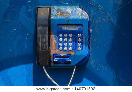 old non-working blue payphone in a booth on the street